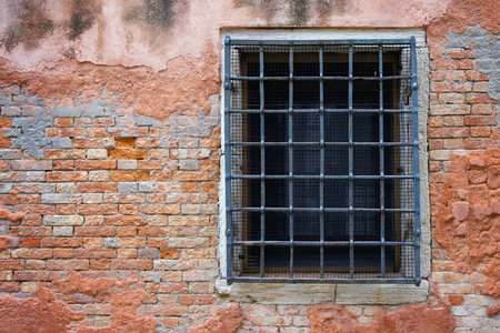 Old window with rusty iron gate on the brick wall facade