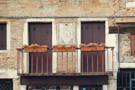 Balcony with flowers on old house brick wall facade