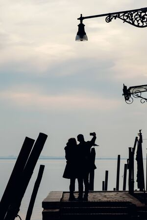 Silhouettes of the couple on the pier taking a selfie