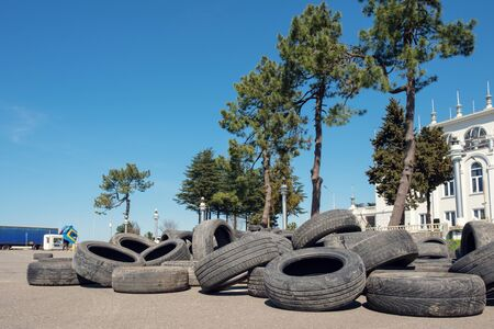 Pile of old car tires on the asphalt, trees and blue sky