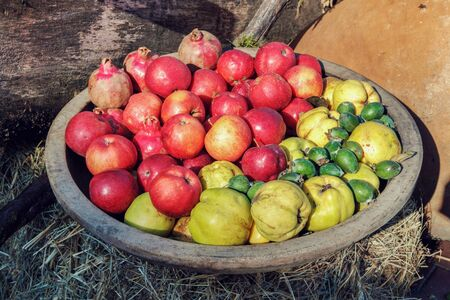 Apples, quinces and kiwi fruits in the wooden bowl Stock Photo