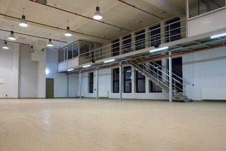 Interior of a  large illuminated empty room with mezzanine