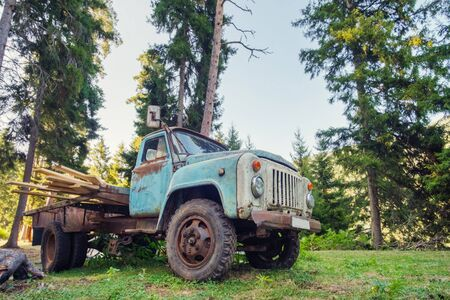 Old rusty truck loaded with logs in the forest