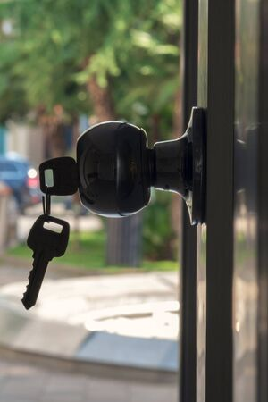 Silhouette of a key in the door lock with blurry outdoor background