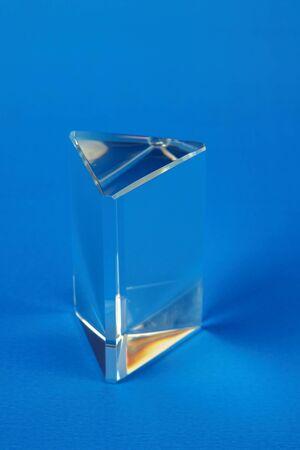 Prisma de vidrio transparente sobre un fondo azul.