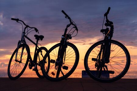 The silhouette of bikes, row of bikes on the beach with sunset cloudy sky background Reklamní fotografie