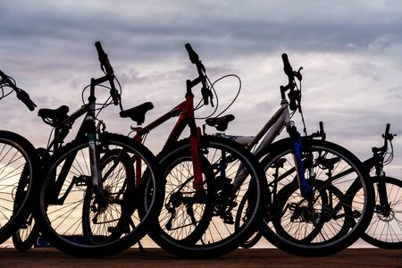 The silhouette of bikes, row of bikes on the beach with cloudy sky background