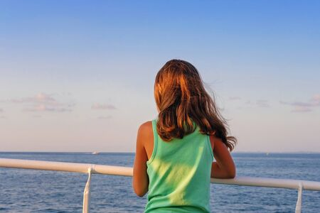 A little girl in green tank top leaning on the railing while looking at the horizon