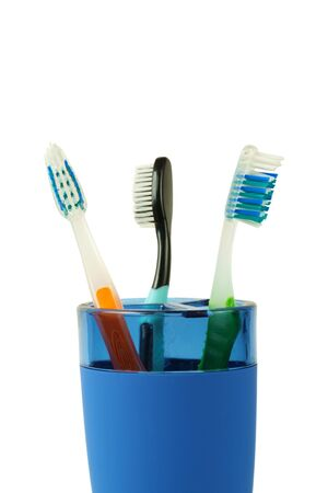 Color tooth brushes in a blue plastic cup, isolated Stock fotó