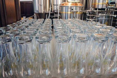 Rows of beer empty glasses resting on a bar ready for serving, Stainless steel brewing tanks. selective focus Foto de archivo