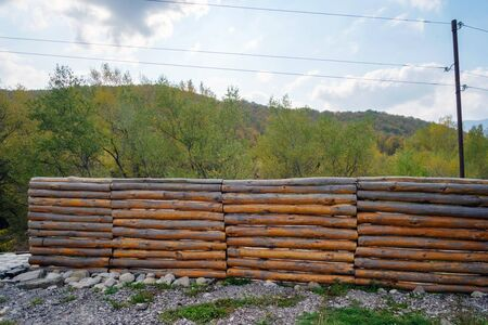 Wooden fence made of logs with forest background Imagens