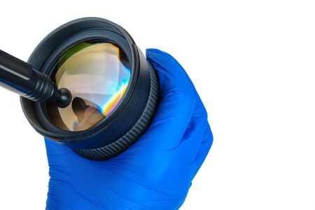 Cleaning digital camera lens, hands cleaning dust from front of lens with a special cleaning pencil, isolated