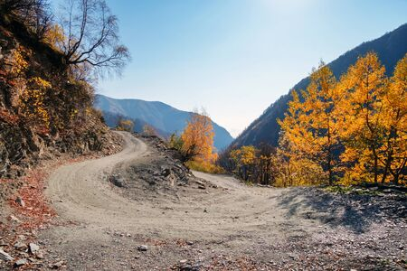 Hairpin turn on highland gravel road with mountains background Stock Photo