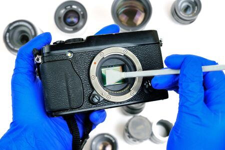 Hands cleaning digital mirrorless camera sensor from dust with swab, blurred background with lenses on white surface