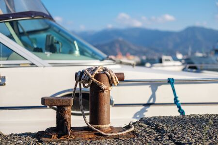Ropes tied to the small steel anchoring bollard, boat mooring lines attached to bollard