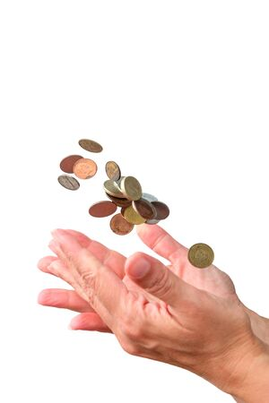 Coins falling down in the palm of a hand, white background isolated