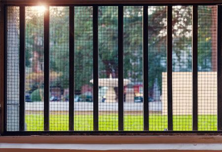 View of the park at sunset through the gridded window, selective focus Foto de archivo