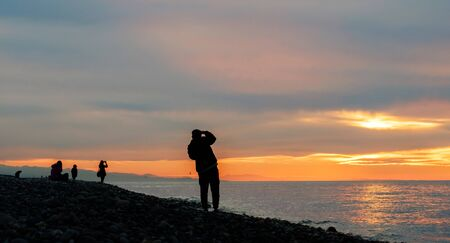 Silhouettes of people taking photos of a beautiful sunset