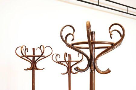 Dettaglio di appendiabiti marrone in legno vintage, sfondo muro bianco