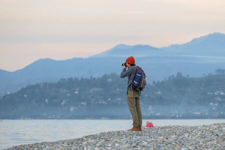 Landscape photographer with backpack taking a picture of sea and mountains at seaside