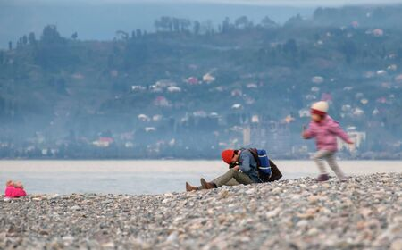 Photographer with backpack taking a macro picture at seaside Banco de Imagens - 138232721