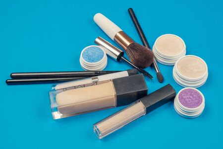 Makeup cosmetics products, brushes and  accessories on a blue surface  版權商用圖片