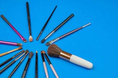 Makeup cosmetics products, set of various make up brushes on a blue background