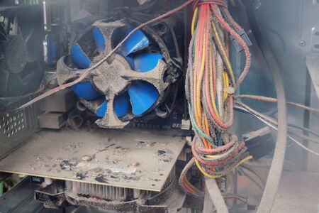 Dust  inside of a broken computer. complication of the PC. Blue fan and other computer boards in the dust.