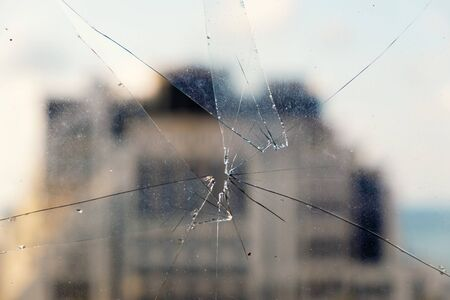 Dirty broken and cracked glass with hole with blurred building background
