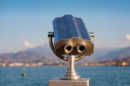 Public stationary binocular on sea shore, Coin operated metal binocular viewer on blurred background sea