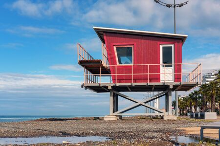 Red lifeguard rescue tower on the beach with blue sky background