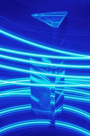 Glass Prism with reflection on a abstract blue neon stripey background Stockfoto