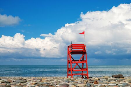 Red wooden lifeguard rescue tower on the empty rocky beach with blue cloudy sky and sea background
