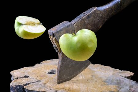 Rusty axe slicing an green apple in half on the wooden board, black background Stock fotó