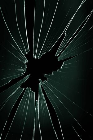 The hole in the broken and cracked glass on a black background