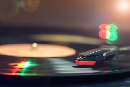 Retro record player with a spinning black vinyl record reflecting green and red lights Reklamní fotografie