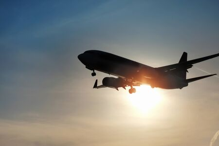 Silhouette of the plane in the sky against the background of the shining sun Stock Photo
