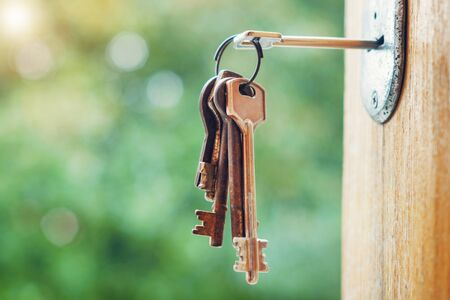 Set of rusty keys in the keyhole with blurred nature background, selective focus