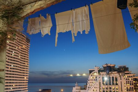 A white laundry hanging to dry in the balcony with night dark blue sky background