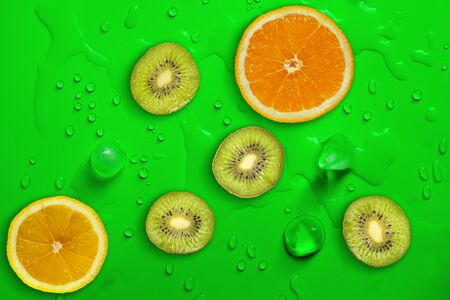 Fresh juicy slices of lemon, kiwi fruit and orange on bright green background covered with water drops. Creative food background, top view