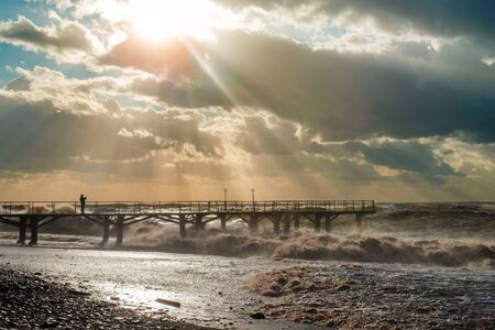 Sunlight breaks through the clouds and illuminating a pier at the stormy beach