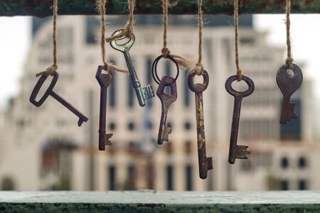 Old rusty keys hanged on the ropes with blurred building background, selective focus 写真素材