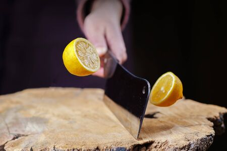 Hand with knife slicing a lemon in half on the wooden board, selective focus