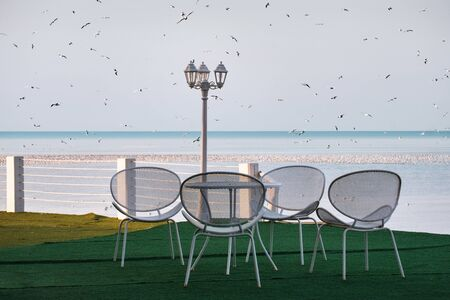 The white metal chairs, table and lamp post on the coast with a background sea and sky full of flock of seagulls