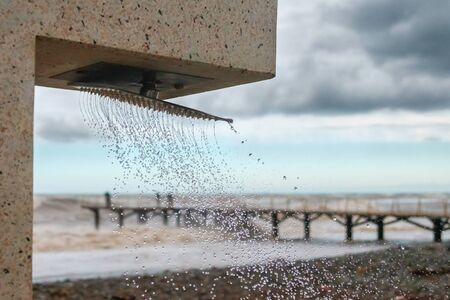 Pouring and splashing water drops from the beach shower with blurred stormy sea and pier background, selective focus 版權商用圖片