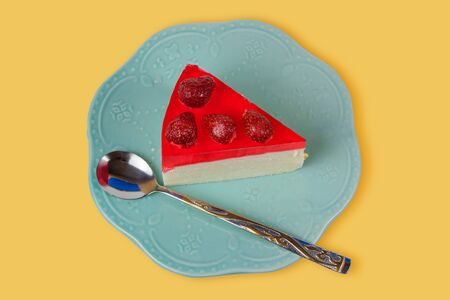 Portion piece of cheesecake with fresh strawberries and strawberry jelly on a vintage teal plate on a yellow surface
