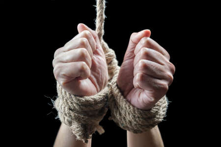 Hands of a victim woman tied up with rough rope on the black background. Stop abusing violence concept Zdjęcie Seryjne