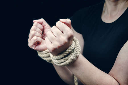 Hands of a victim woman tied up with rough rope on the black background. Stop abusing violence concept 스톡 콘텐츠