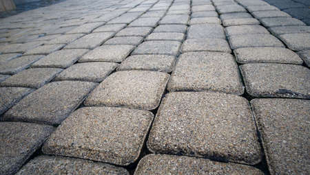Detail of vintage traditional stone pavement in perspective. Abstract background of old cobblestone pavement