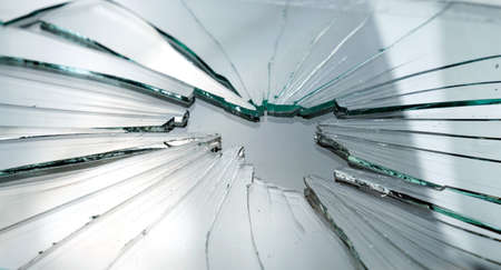 Closeup of broken and cracked glass with hole
